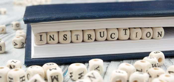 Libro azul con bloque de madera con la palabra Instruction