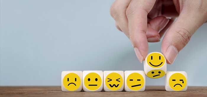 Una mano toma cubos con emoticones de diferentes emociones