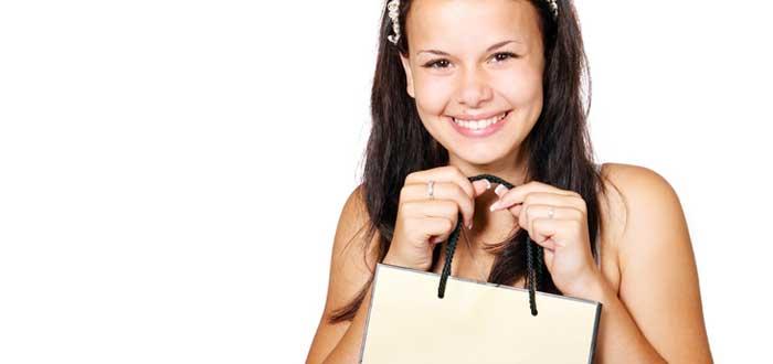 Mujer joven sonríe con una bolsa de compras en la mano