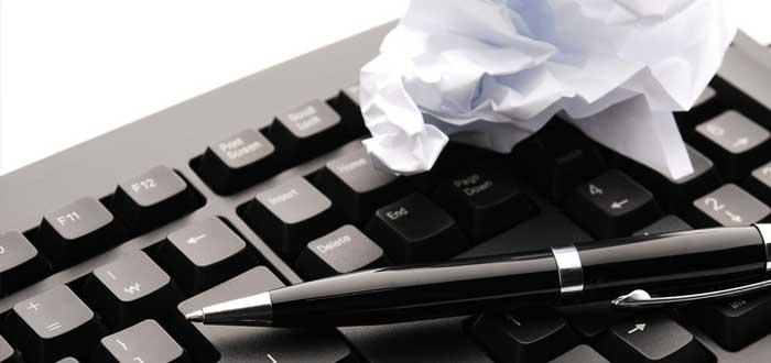 Teclado de computadora y papel arrugado