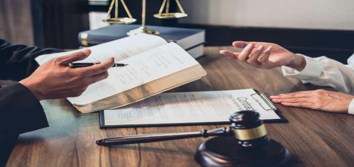Abogado consultando documentos y asesorando a una persona