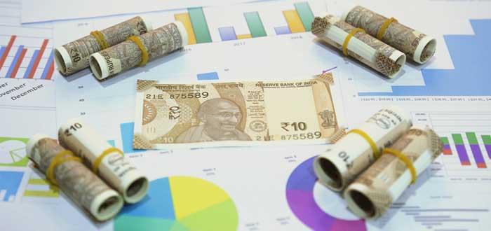 Billete y dinero en rollos con gráficos de viabilidad financiera