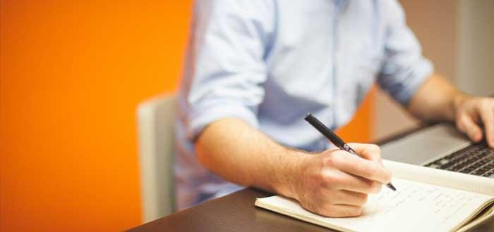Emprendedor escribe en un cuaderno su plan estratégico