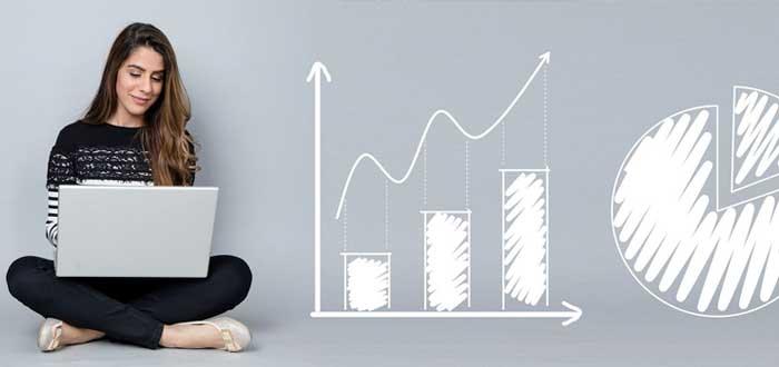 Empresaria con laptop y gráficos sobre viabilidad financiera