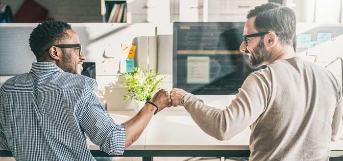 Empresarios chocan puños frente a computadoras