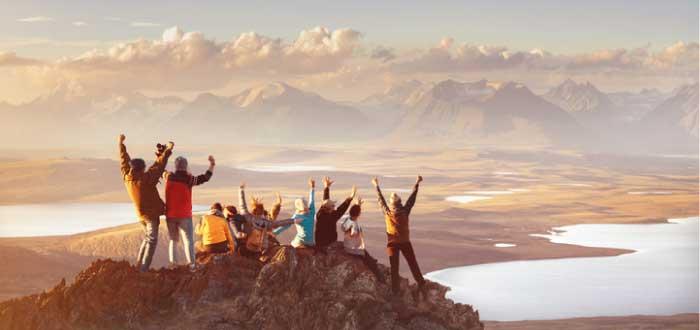 grupo de personas felices en la cima de una montaña