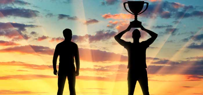 hombre sosteniendo un trofeo y otro a su lado mirándolo