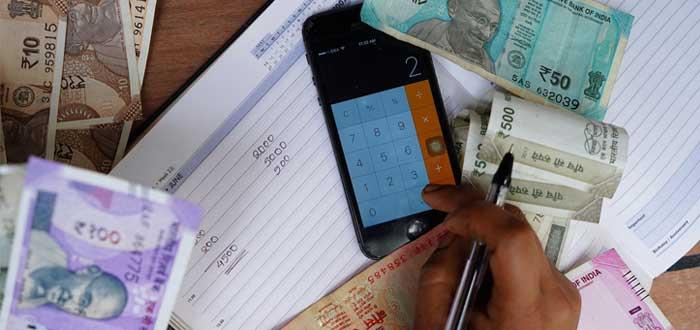 Mano hace cálculos en libreta con billetes alrededor