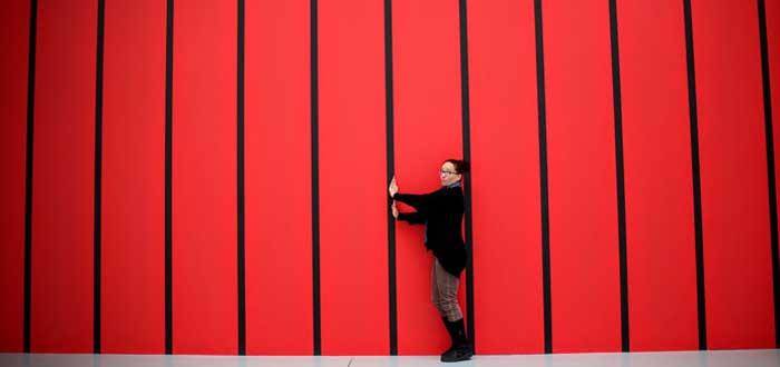 Mujer con barras sobre fondo rojo