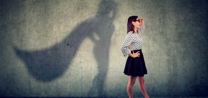 mujer de pie con una sombra detrás que refleja su fortaleza
