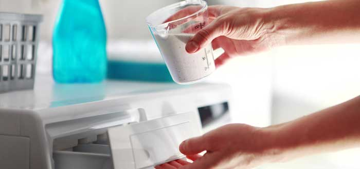 Una mujer pone detergente en la lavadora
