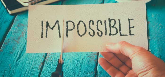 persona cortando con unas tijeras la palabra imposible porque esta es una de las razones por las que nunca rendirse