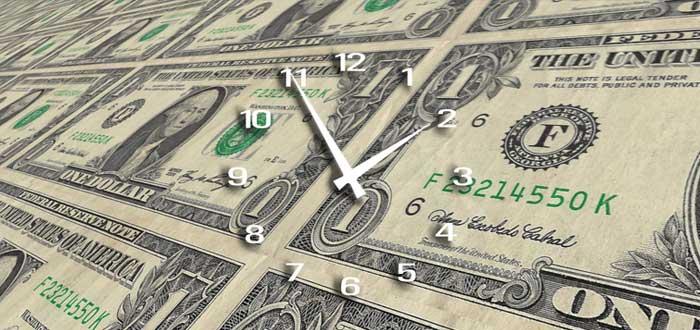 Reloj sobre billetes de dólares que representa las formas de perder el tiempo de un emprendedor
