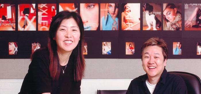 Do wong chan y su esposa posan y en el fondo una pared con fotografías de moda