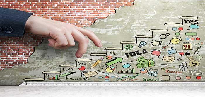 Mano subiendo un dibujo de escalera que contiene objetos característicos de los emprendedores