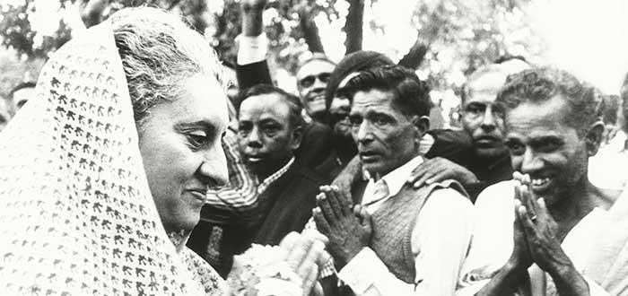 Retrato en blanco y negro de Indira Ghandi con algunos de sus seguidores al fondo