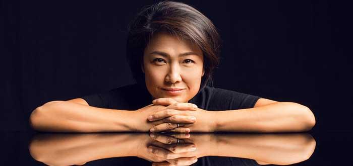 Retrato de Zhang Xin con los brazos apoyados sobre una superficie y su baribilla apoyada sobre los dedos entrelazados, con el fondo oscuro