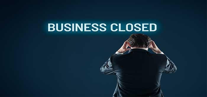 emprendedor agobiado por su fracaso, de espaldas, vestido de traje, se sujeta la cabeza mientras mira un letrero que dice business closed