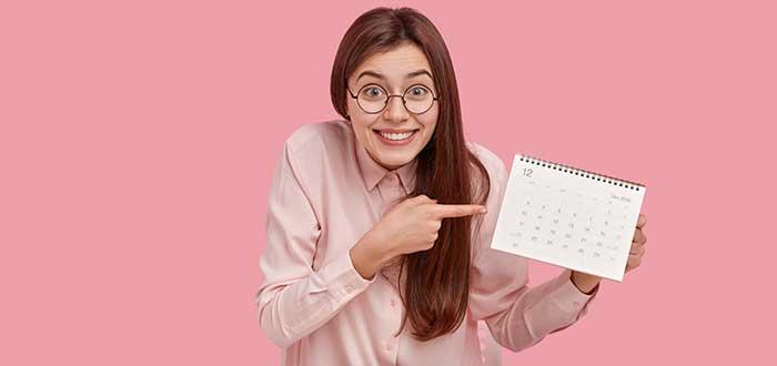 Chica vestida de rosa y con lentes apunta a un calendario, sobre un fondo rosado