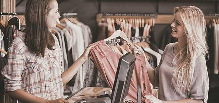 Chica compra una blusa en una tienda mientras la cajera la atiende, ejemplo de plan de ventas