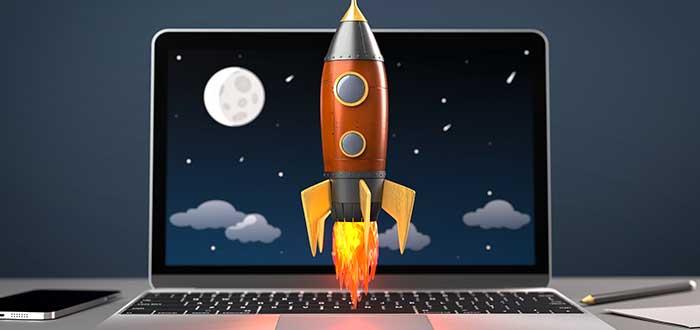 Cohete despega sobre un ordenador portátil ubicado en un escritorio, junto a un teléfono
