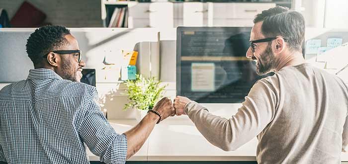 Dos compañeros celebran chocando el puño el éxito del emprendedor