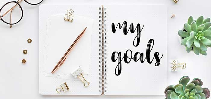 """cuaderno con la frase """"my goals"""" escrita, bolígrafo, plantas y lentes sobre un escritorio"""