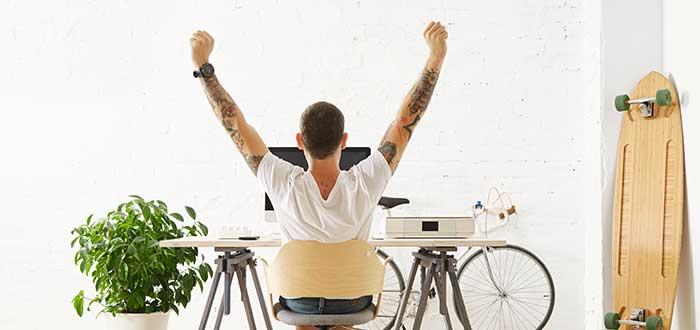 Hombre vestido casual celebra sentado frente a su escritorio con una tabla y una bicicleta a su alrededor, un ejemplo de otro de los tipos de liderazgo