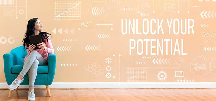 """Mujer sentada sobre un sillón azul y en el fondo una pared color durazno en la que hay diferentes dibujos y se lee la inscripción """"unlock your potential"""""""