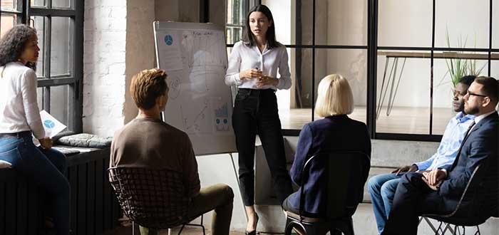 Equipo de trabajo reunido en la oficina liderado por una mujer
