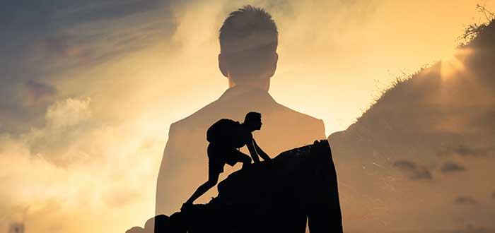 hombre determinado a superar los fracasos del emprendedor escala una montaña mientras su silueta lo observa