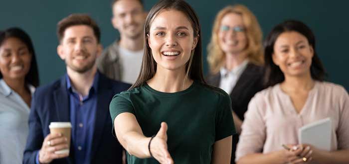 Mujer sostiene la mano para apretón mientras la acompaña un equipo de profesionales que evidencia la diversidad en las empresas