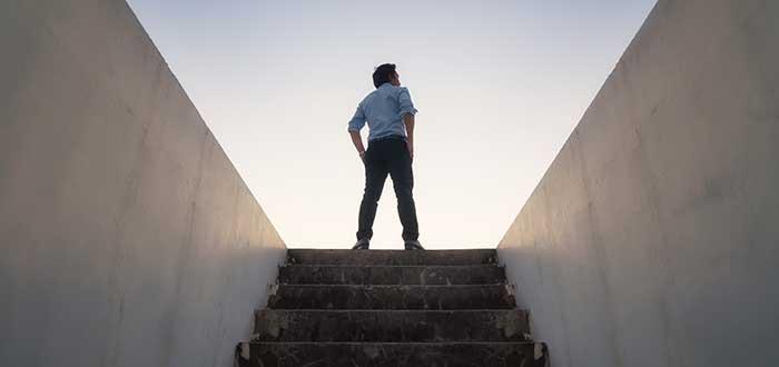 Hombre parado en la cima de una escalera cuyas paredes forman un angulo que se asocia con la visión empresarial
