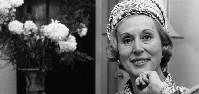 fotografía en blanco y negro de la empresaria Estée Lauder posando junto a unas flores