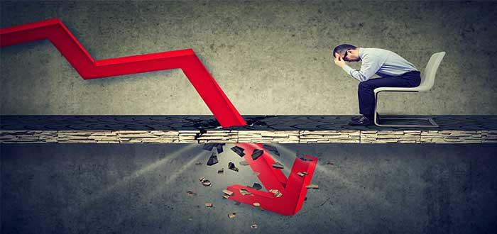 emprendedor fracasado sentado con la cabeza entre las manos y flecha roja con tendencia a la baja que atraviesa el suelo