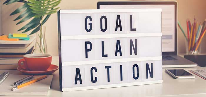 """Letrero blanco sobre un escritorio con las palabras """"goal, plan, action"""" y objetos varios en el fondo"""