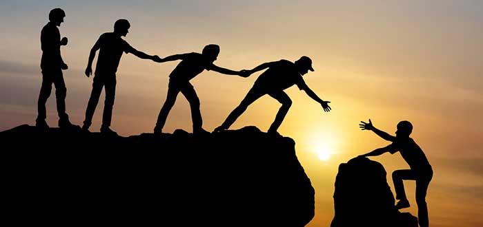 grupo de personas del que unicamente se ve su silueta ayudan a otra persona a cruzar una montaña