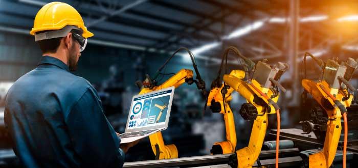 hombre frente a línea de producción automatizada