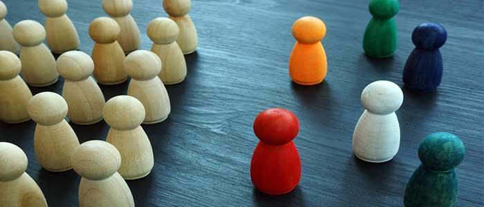 fichas de madera iguales enfrentadas a fichas de madera coloridas, que simbolizan los tipos de liderazgo
