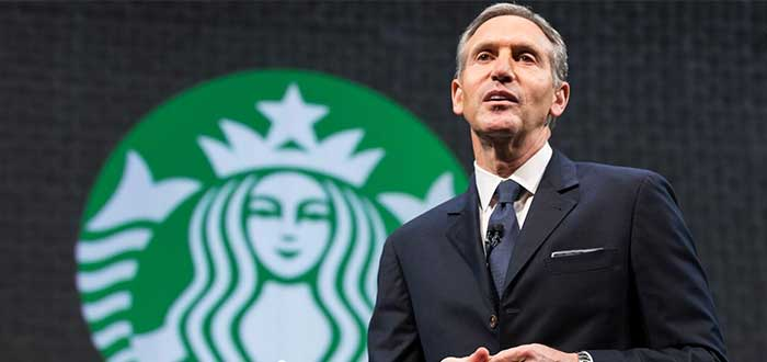 Howard Schultz vestido de traje con el logo de Starbucks al fondo