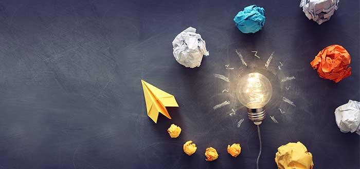 Bolas de papel de diferntes colores y un avión de papel amarillo rodean el dibujo de una bombilla sobre un fondo negro