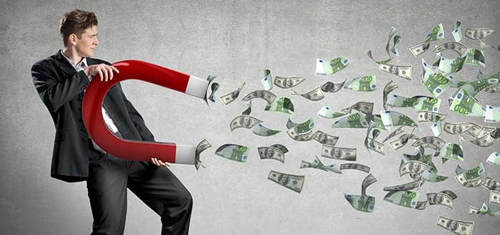 hombre ejecutivo sostiene un imá que atrae dinero, representando las historias de personas exitosas
