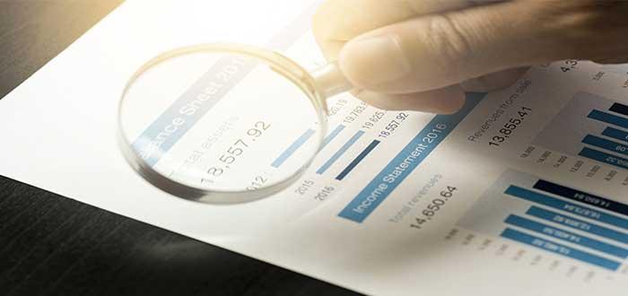 mano con lupa sobre un papel con diferentes datos en un plan de ventas