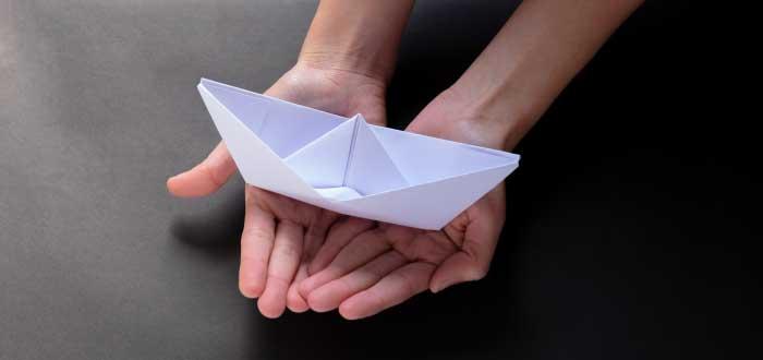 palmas de las manos sosteniendo un barquito de papel