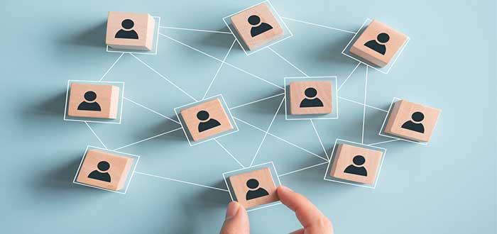 bloques de madera con iconos de personas interconectados por una red. Una mano sujeta a uno de ellos