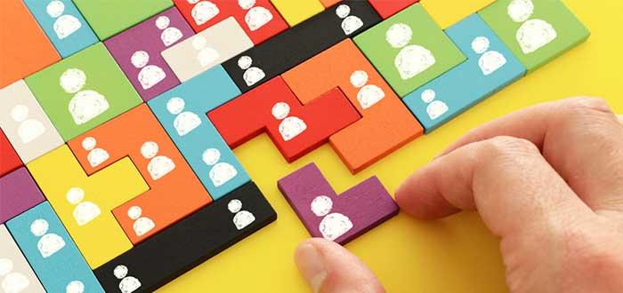 mano arma un rompecabezas multicolor de fichas con icono de personas en mano