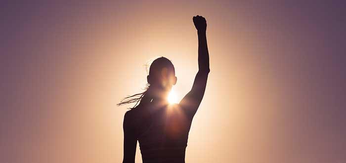 Silueta de mujer levanta el puño derecho