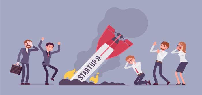 cohete que dice startup estrellado en el suelo mientras las personas alrededor se lamentan por el fracaso de su emprendimiento