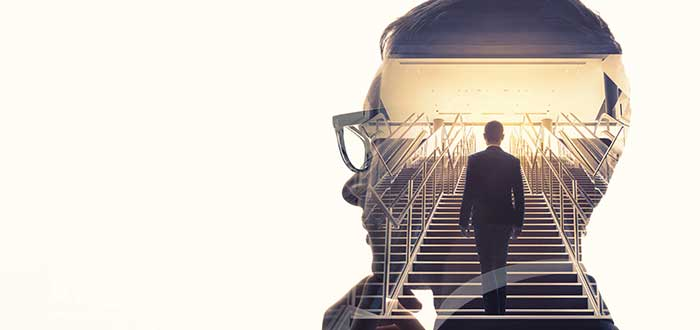 silueta de cabeza de hombre de negocios y a través de él se ve a un hombre de traje subiendo una escalera