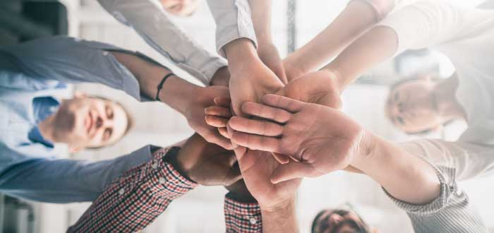 empleados uniendo las manos en el centro
